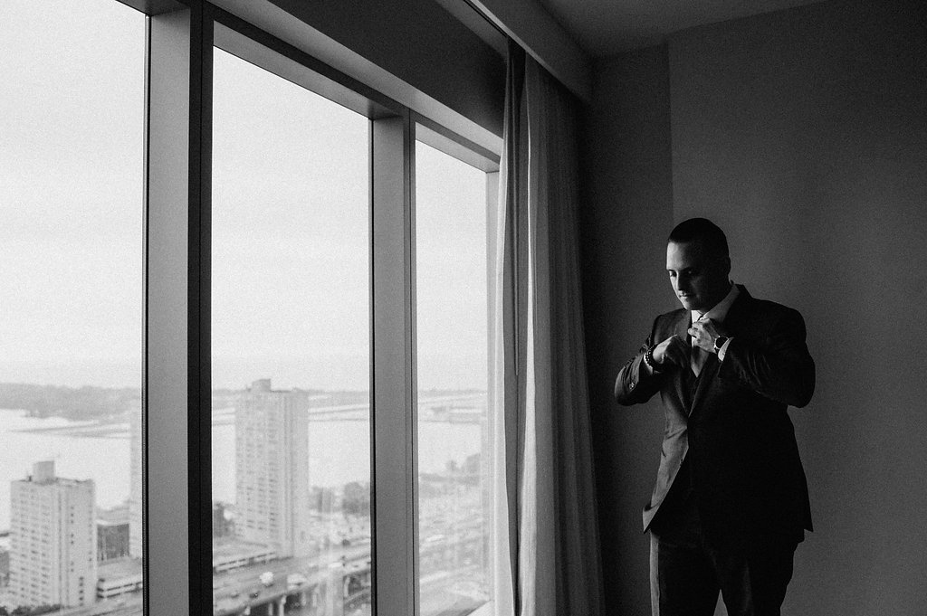 moody black and white groom photo with Toronto skyline