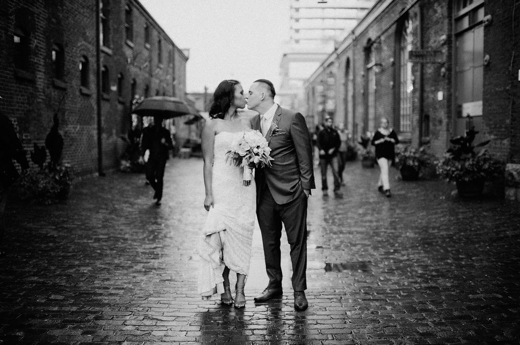 black and white rainy photo of bride and groom