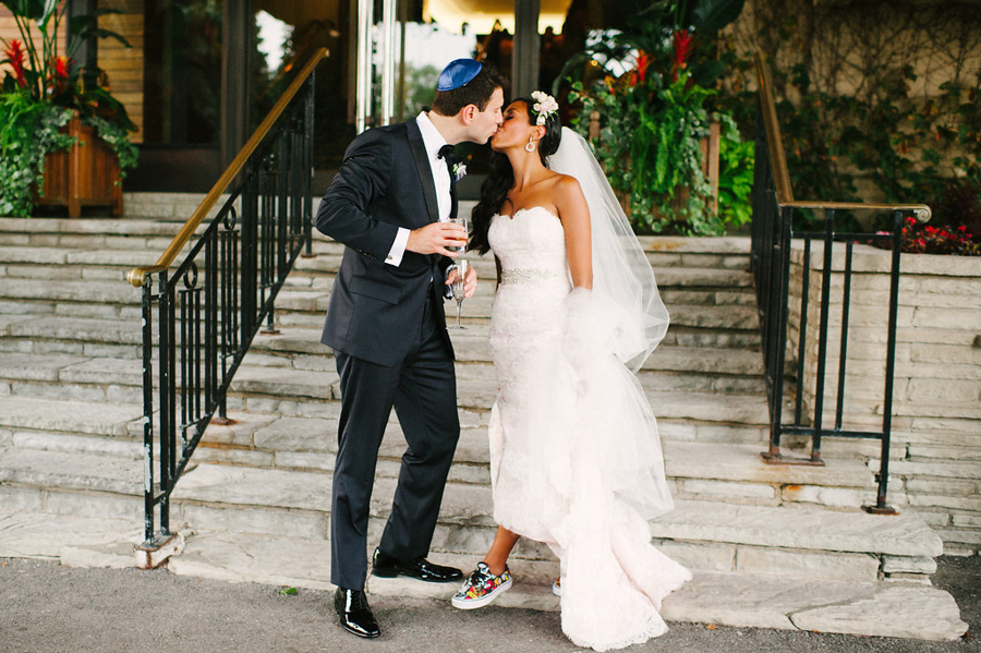 Jewish bride and groom kiss as bride shows off sneakers