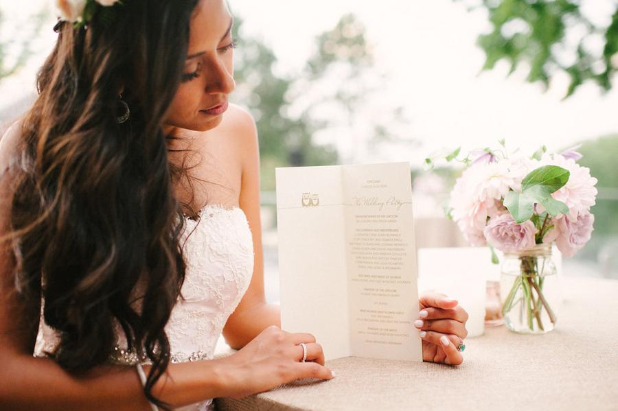 bride holding her wedding program in soft pink