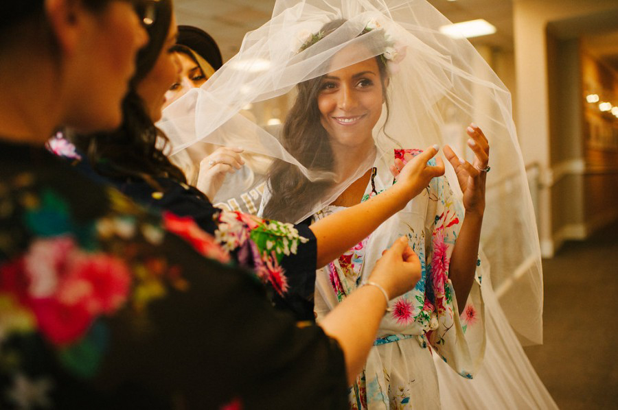 bridesmaids help smiling bride with her veil