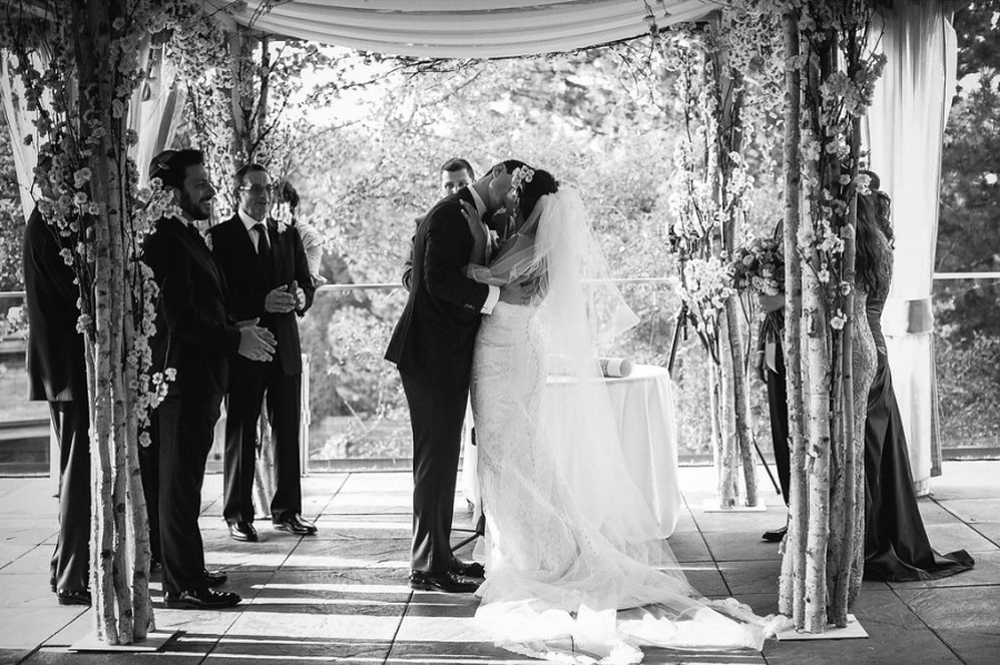 bride and groom kiss under Chuppah in black and white