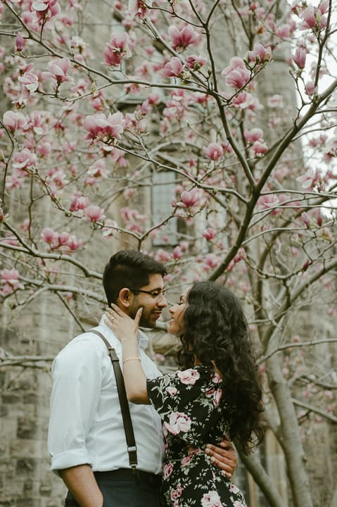 A bride and groom embrace under a cherry blossom tree in Toronto