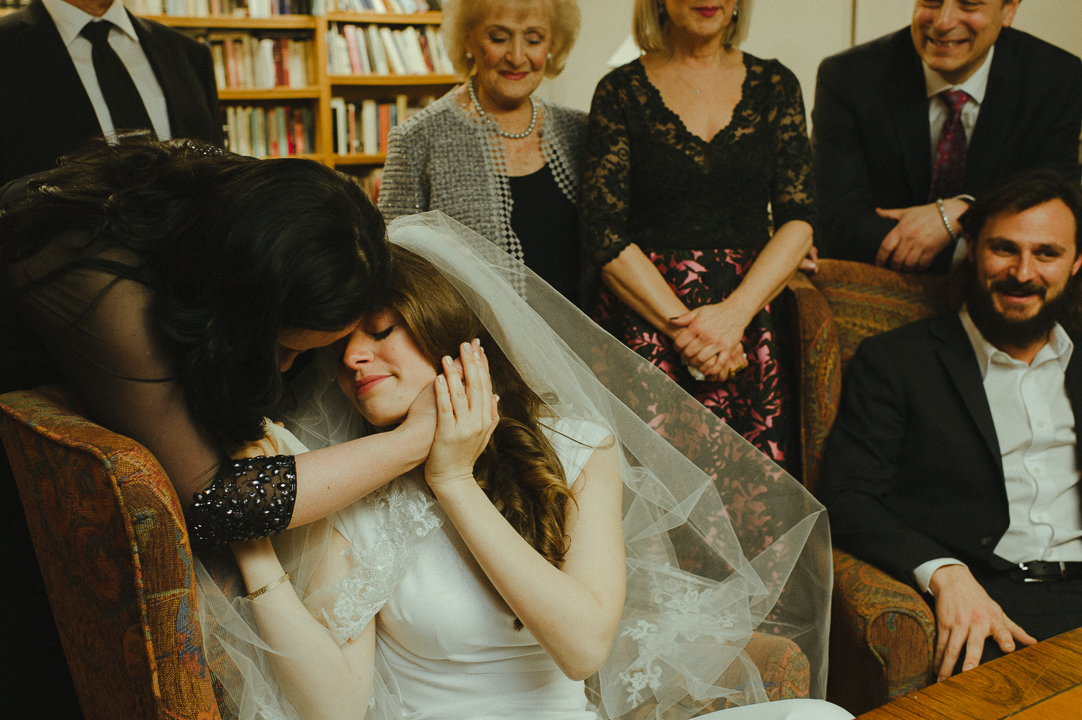 A bride's mother whispers words of love and blessing into her daughter's ear during her bedeken.