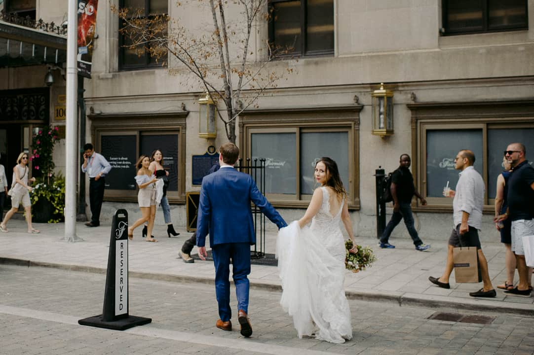 bride and groom walk outside Fairmont Royal York Hotel
