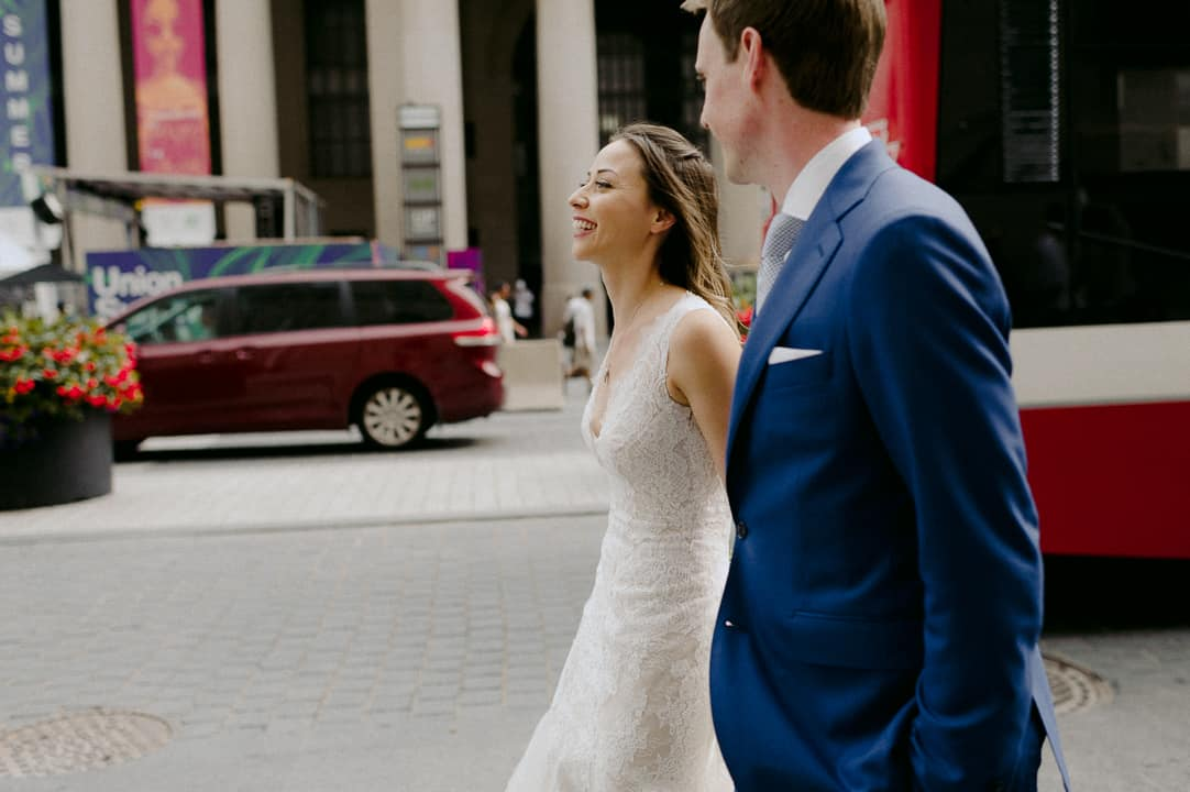 bride and groom walk outside Fairmont Royal York Hotel with TTC