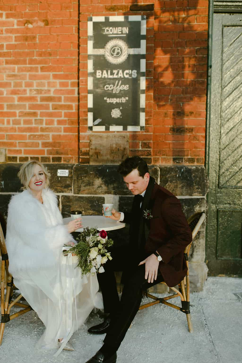 Bride and Groom sit in front of Balzacs before their Distillery District wedding.